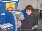 Fox Chase postal customer, Janice Mundy, uses the Automated Postal Center to mail her packages.